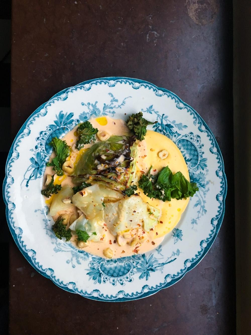 smörbakad kål med äggkräm, harissagrädde, grönkålschips och hasselnötter